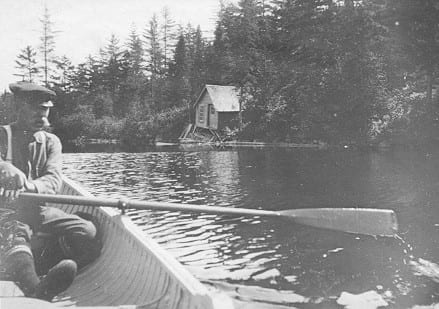 black and white photo of man paddling canoe in river