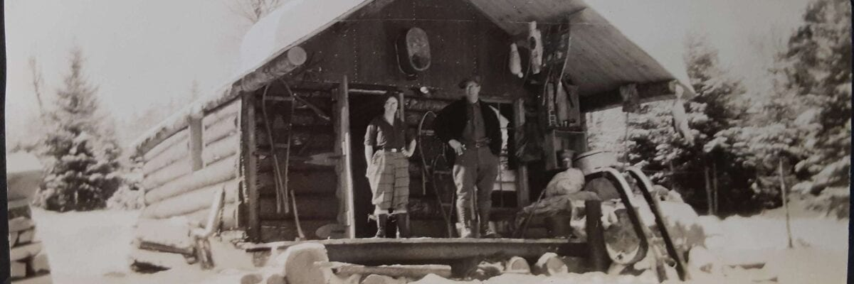 black and white photo of two men standing in front of cabin in winter