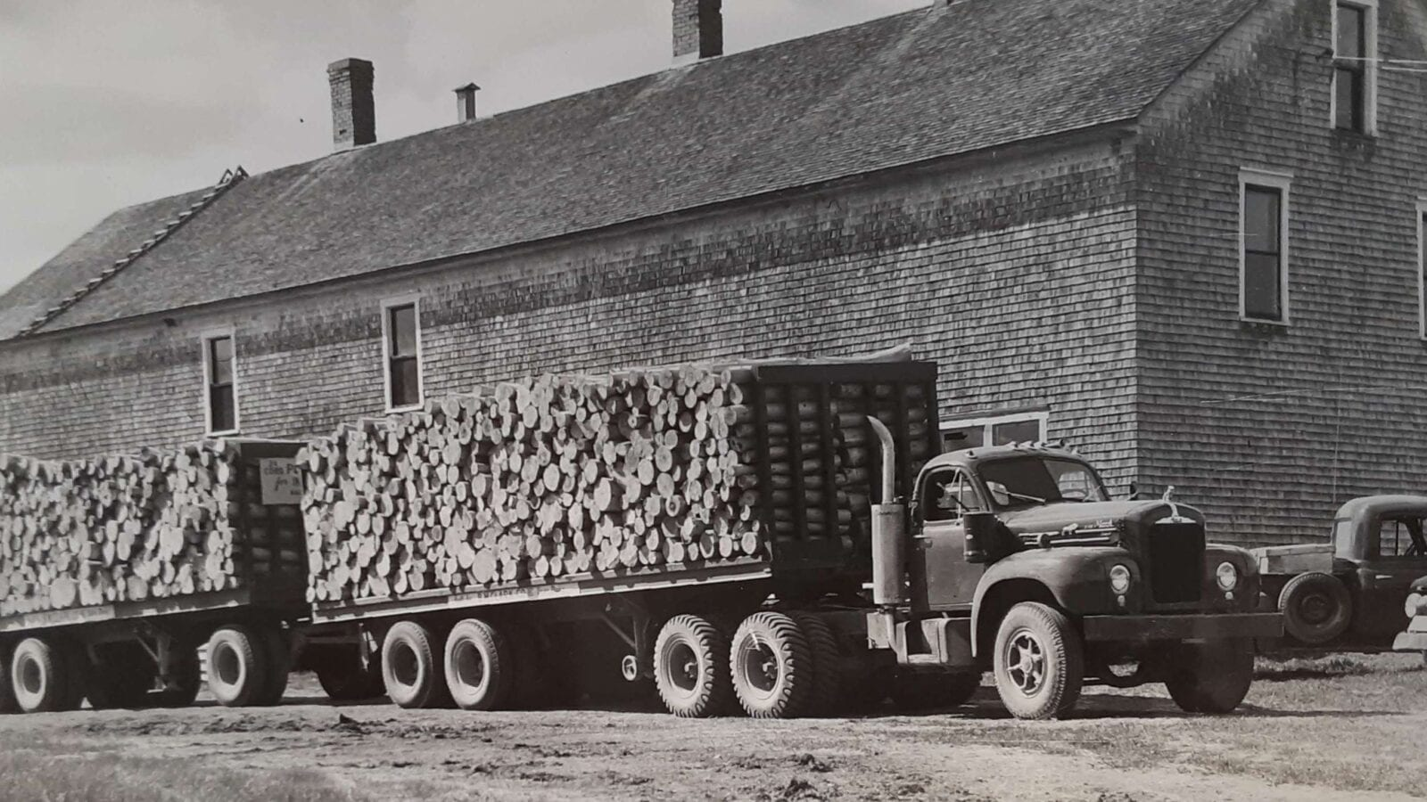 black and white photo of logging truck full of logs