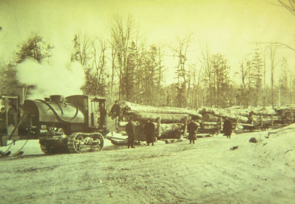 black and white photo of log hauling train in winter