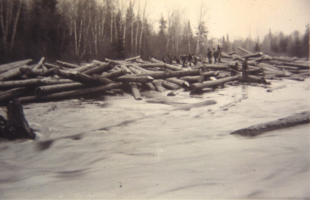 black and white photo of men driving logs down river