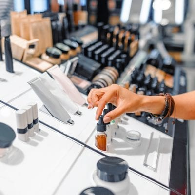 woman chooses cosmetics and make-up products in a store
